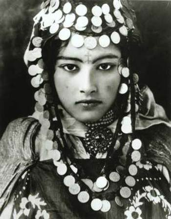 This early 20th-century photograph is of a Tunisian Berber girl, whose mirrored sequins are similar to the ones on the Moroccan blankets; her forehead tattoo is a common symbol used to ward off evil