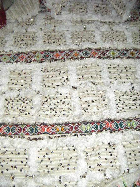 Often, a handira is accented with colorful bands of woven wool, on the topside or the underside